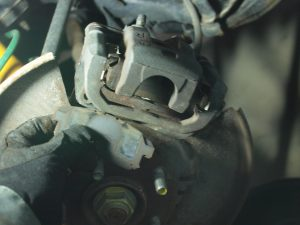 Remove old pads off of the caliper.  Then remove the bolts holding caliper on caliper bracket.
