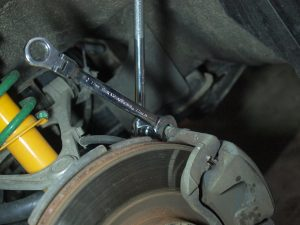 Use 17mm open wrench and 14mm socket on breaker bar to loosen / remove the bolt holding caliper.