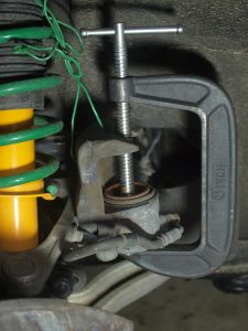 Clean the rubber boots on caliper piston, use a large C-Clamp, slowly press the piston back.
