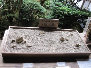 The famous Stone Garden of Ryo-an-ji.  This is a touchable scaled model, and only way to see all 15 rocks at the same time
