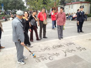 a old guy was showing off his calligraphy using a big brush.