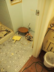 Remove the toilet, and then stuff newspaper to keep tools and dirt from falling in.