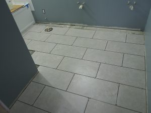 First, I tried, but found Rick does much better job, faster, installing those floor tiles.  I was being a good assistant by mixing thin set, cutting and buttering the tiles while he install them.